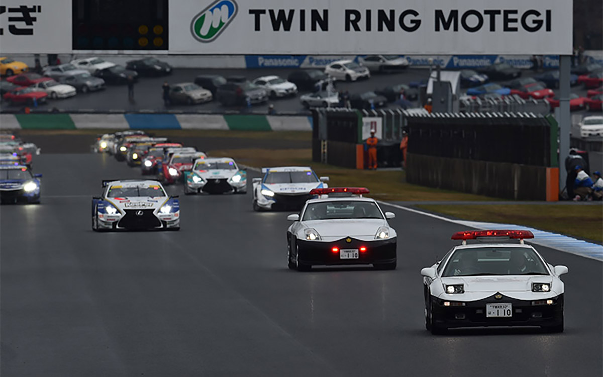 Japanese Police Cars Escorting Race Cars in The Circuit